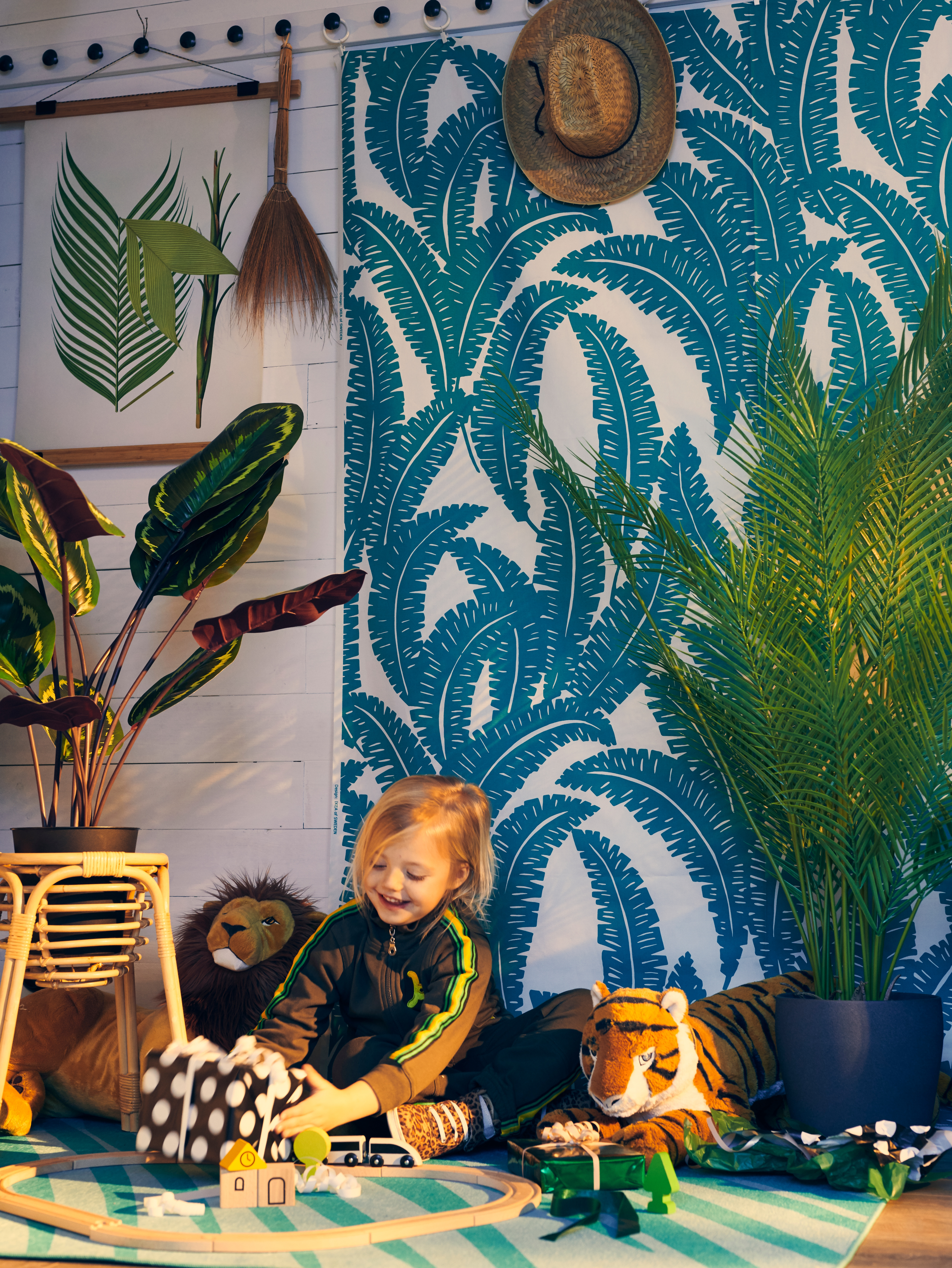A child holding a present by two wild animal soft toys. The wall behind is covered in UGGLEMOTT fabric, with plants nearby.