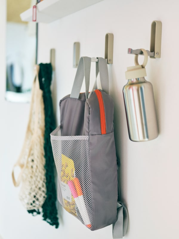 A light-grey PIVRING backpack hangs along with various accessories on a row of wall-mounted KLYKET folding hooks.