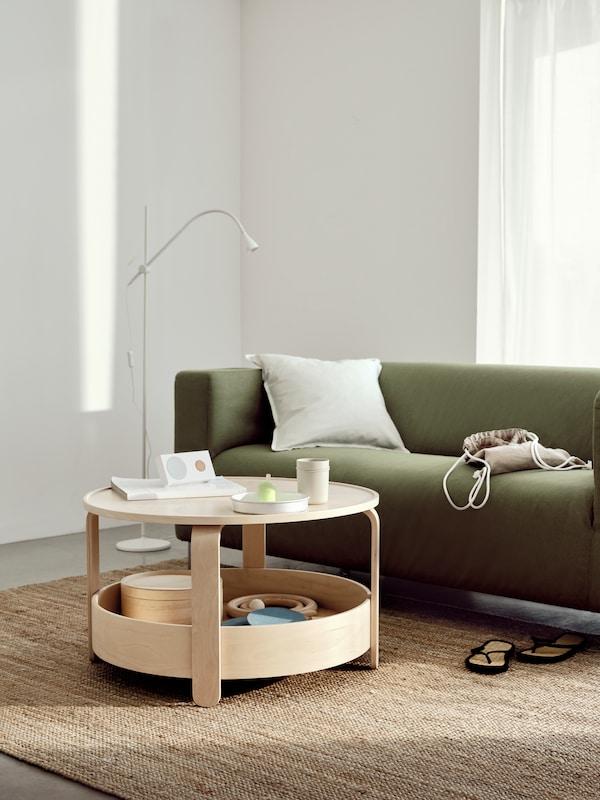 BORGEBY-kahvipöytä on nähtävissä aurinkoisessa, valkoisessa olohuoneessa vihreän KLIPPAN-SOHVAN vieressä.