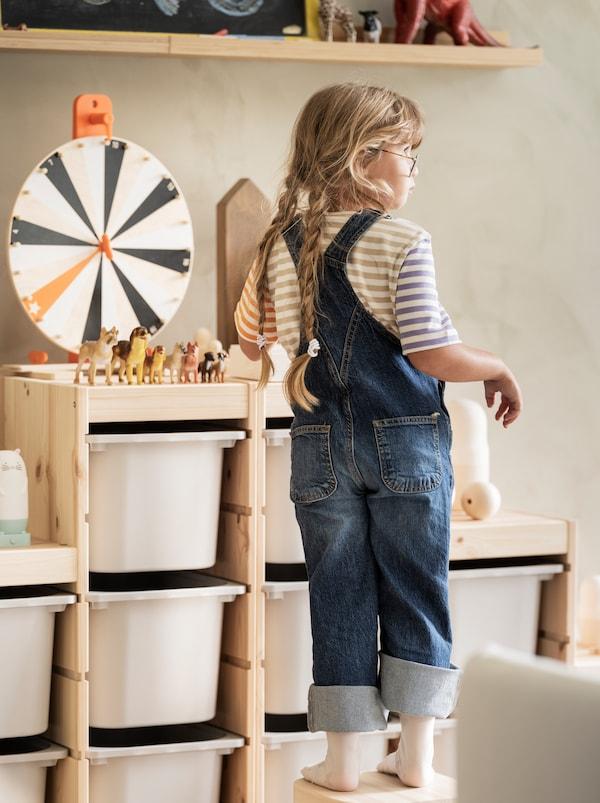 Ein Kind steht neben einer TROFAST Aufbewahrungskombination, auf dem ein LUSTIGT Spiel und Stofftiere zu sehen sind.