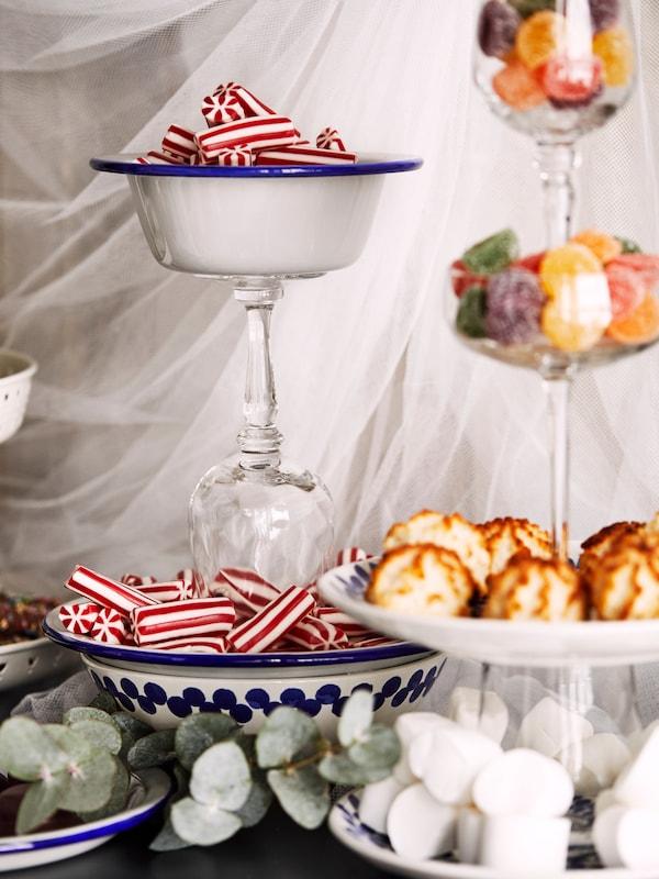 Una exposición creativa de platos, copas y cuencos, pegados unos sobre otros y llenos de diferentes tipos de dulces.