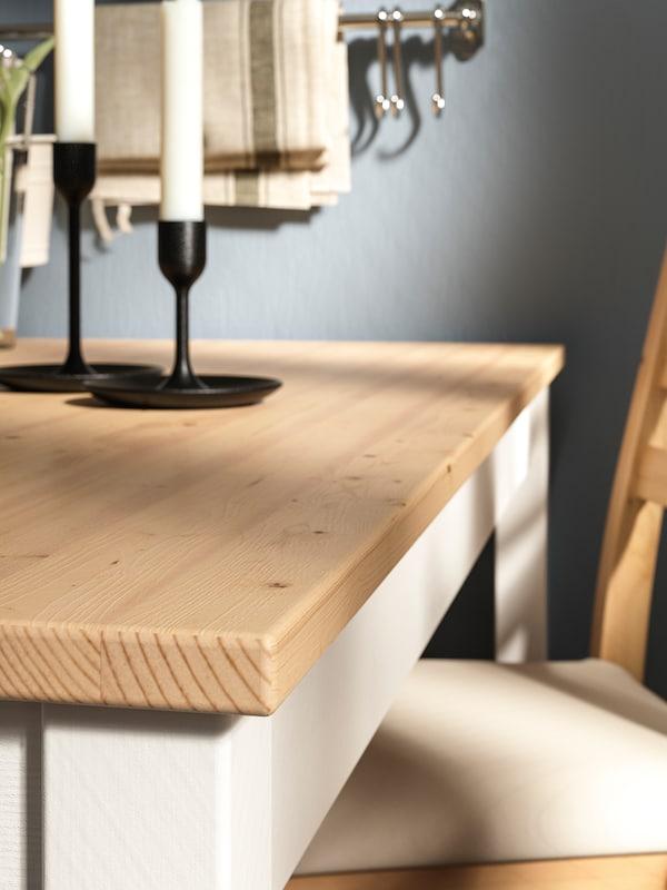 Rahlo pobeljena LERHAMN mizna plošča, na kateri sta dva črna svečnika, in del stola, ki se ujema z mizo.
