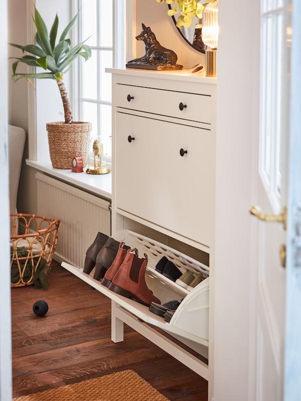 Una scarpiera HEMNES bianca con cassetto aperto e 5 paia di scarpe. Sullo sfondo una pianta con vaso sul davanzale e sotto un cestino.