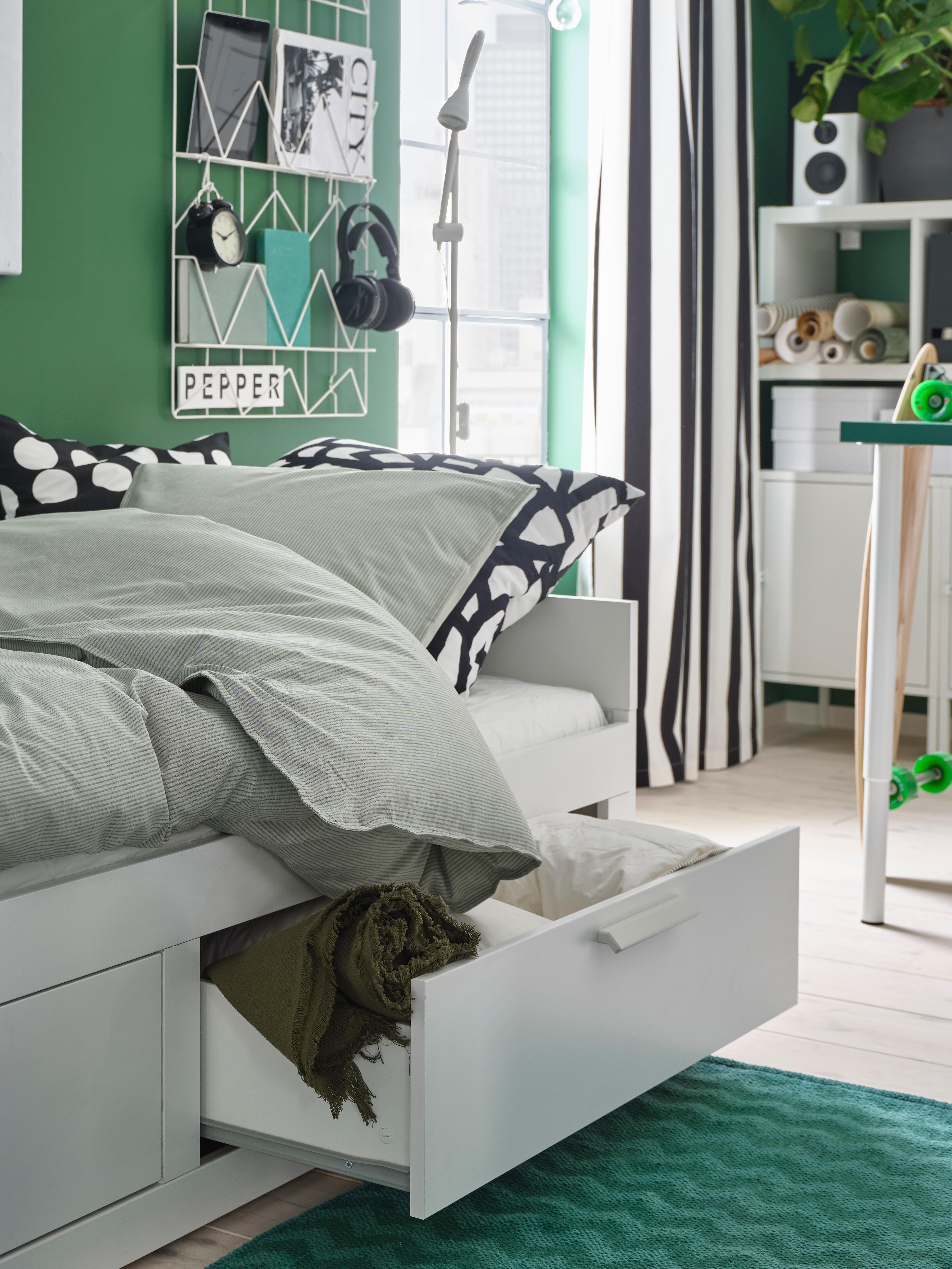 Šarena soba u kojoj je BRIMNES bijeli dnevni krevet s dvije ladice. Jedna ladica je otvorena, prikazuje posteljinu i laganu deku unutra.
