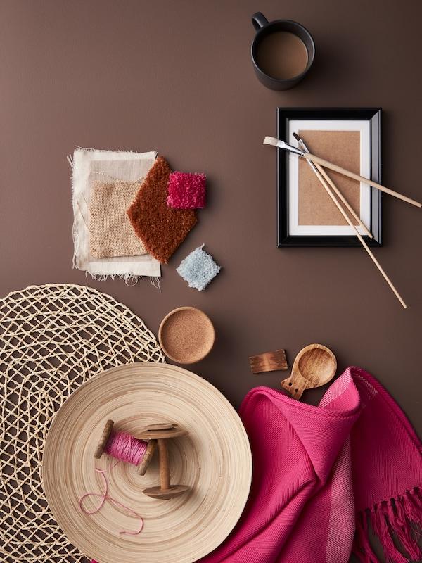 Egy rózsaszín HILLEGÄRD takaró és egy bambusz tál egy pálmalevélből készült tányéralátéten, anyagminták és egy kis fekete keret társaságában.