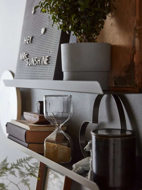 Wall-mounted, dark-grey MALMBÄCK shelves with a plant pot, a memo board and various art. A TROMMA clock on the wall beside.