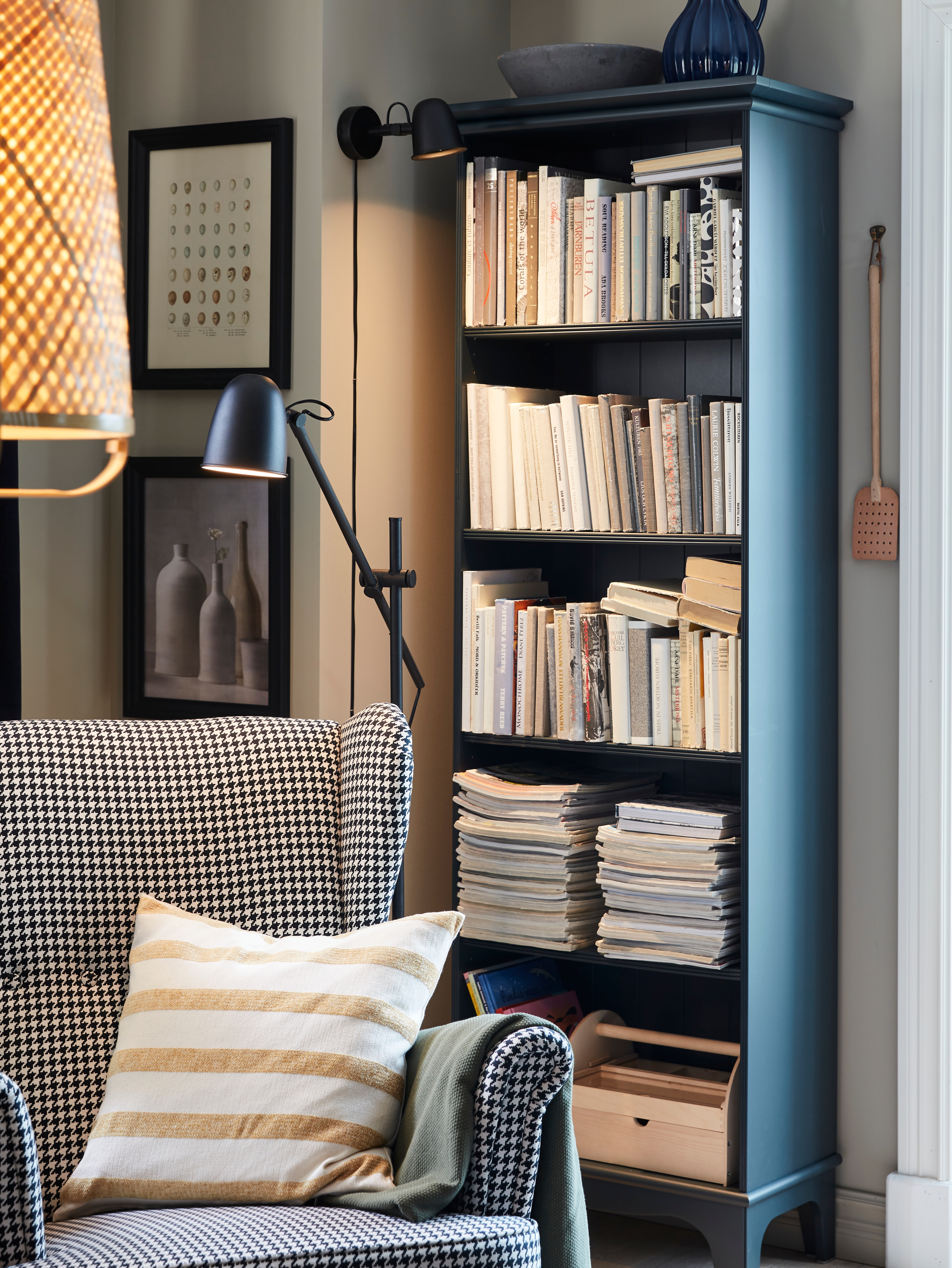 A reading corner has a black SKURUP floor/reading lamp shining down on an armchair by a bookcase and a matching wall lamp.