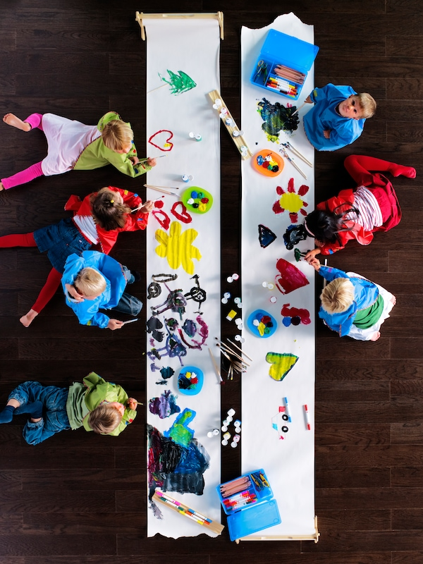 A lot of children lie on the floor painting with MÅLA brushes and paint on long pieces of MÅLA drawing paper roll.