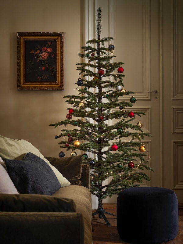 A large holiday tree stands in a traditional-looking living room, its branches decorated with bright-coloured baubles.