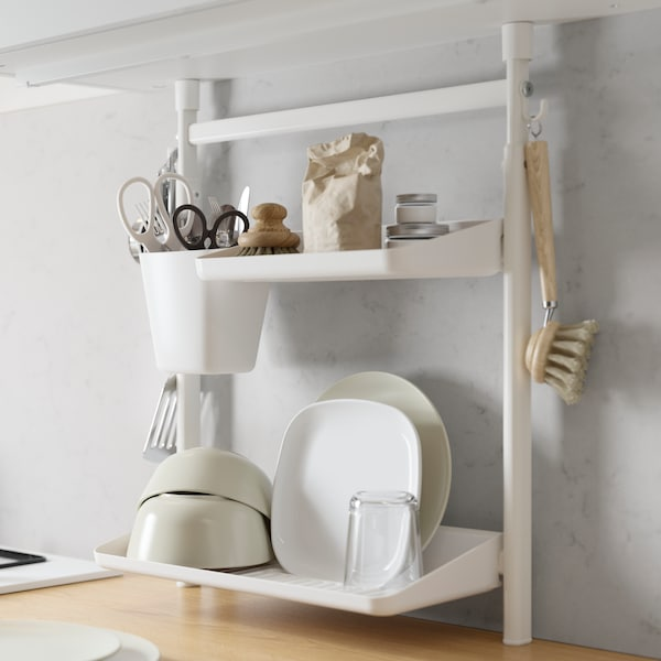 A SUNNERSTA kitchen organiser set holding clean bowls and plates, with a container hanging from the side with scissors.