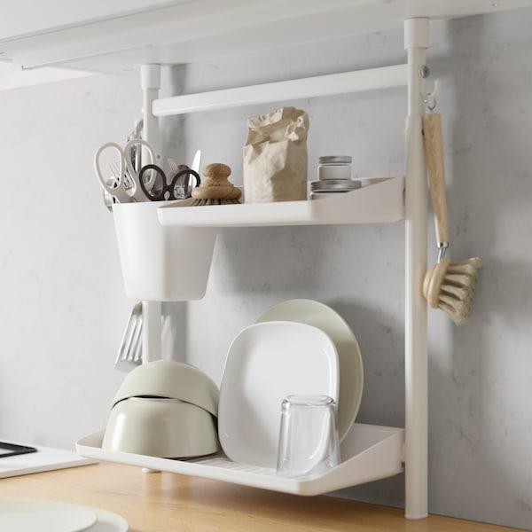 Súprava s poličkami do kuchyne SUNNERSTA, na poličkách sú čisté misky a taniere a naboku zavesená nádobka s nožnicami.