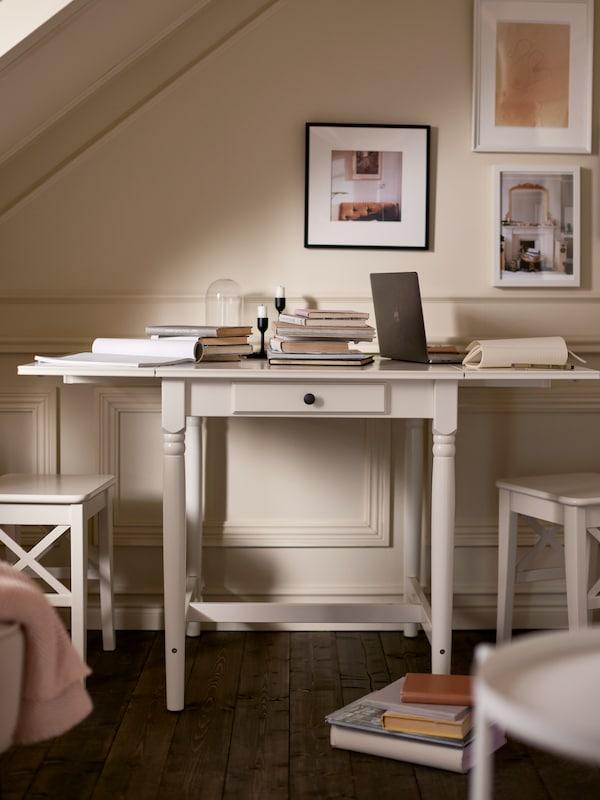 Egy fehér INGATORP lehajtható lapú asztal könyvekkel és egy laptoppal, egy világos fal előtt, melyen keretezett képek lógnak.