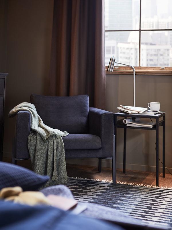كرسي بذراعين KOARP مع بطانية على الذراع الأيمن، بجانب طاولة جانبية NYBODA مع مصباح قراءة وكوب وأوراق في الأعلى.