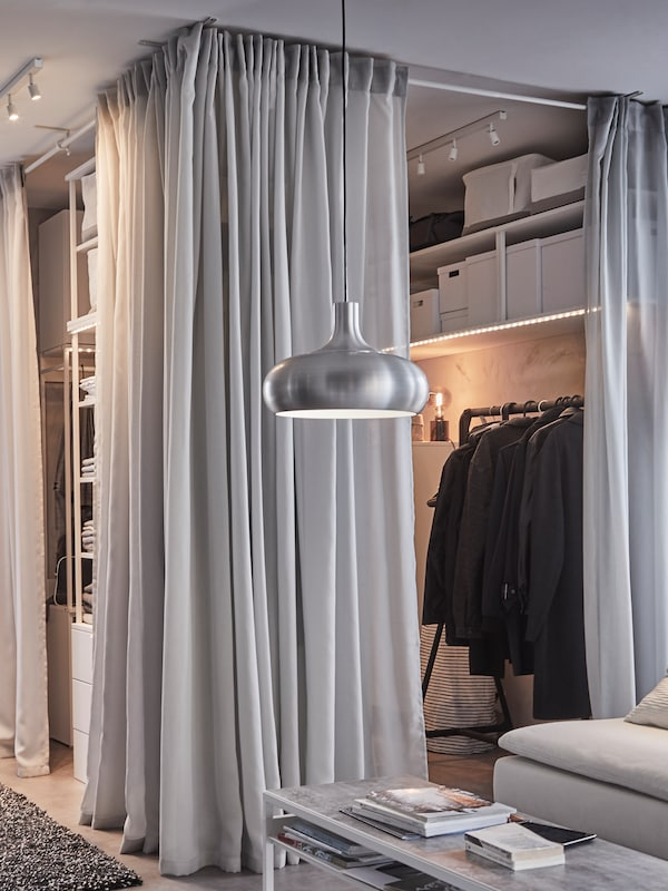 An open wardrobe solution, light grey GUNRID curtains, a black clothes rack and a VÄXJÖ aluminium coloured pendant lamp.
