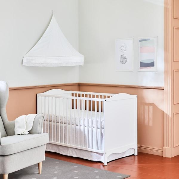 سرير أطفال SMÅGÖRA أبيض في زاوية غرفة مع مظلة سرير على الحائط فوقها وبالقرب من كرسي بظهر مرتفع وجوانب بارزةSTRANDMON.