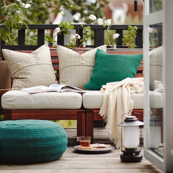 Et udsyn til en altan med en sofa af træ med lyse hynder og lyse og grønne puder. På gulvet står en grøn, lav puf til brug udendørs.