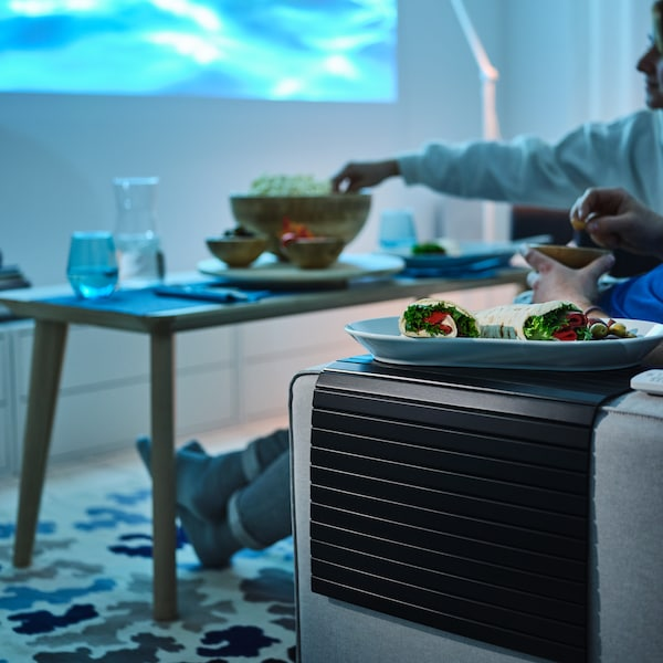 A meal on a white IKEA 365+ serving plate sits on a black RÖDEBY tray on the armrest of a light-grey KIVIK two-seat sofa.