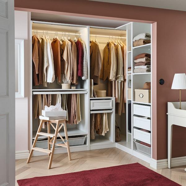 Un armario de esquina PAX blanco en una habitación rosa con cajones KOMPLEMENT y ropa colgada en barras. Delante hay una escalera BEKVÄM.