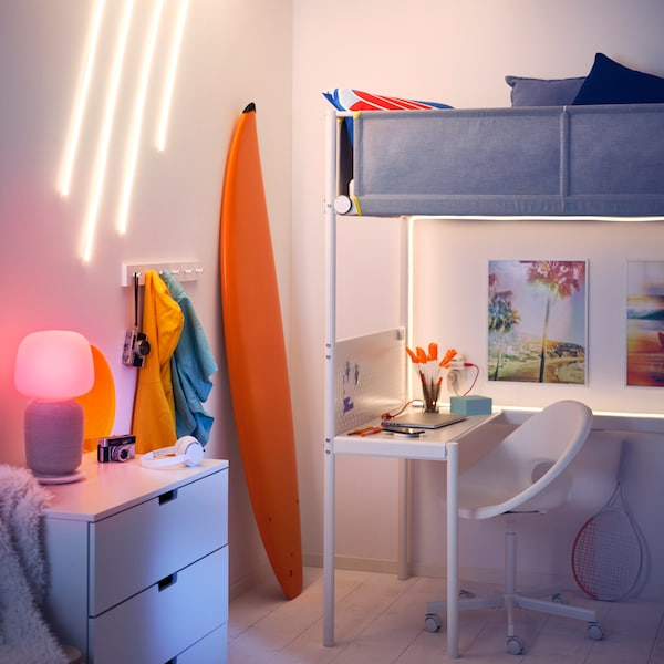 MICKE desk in white with a book, a notepad and a computer.