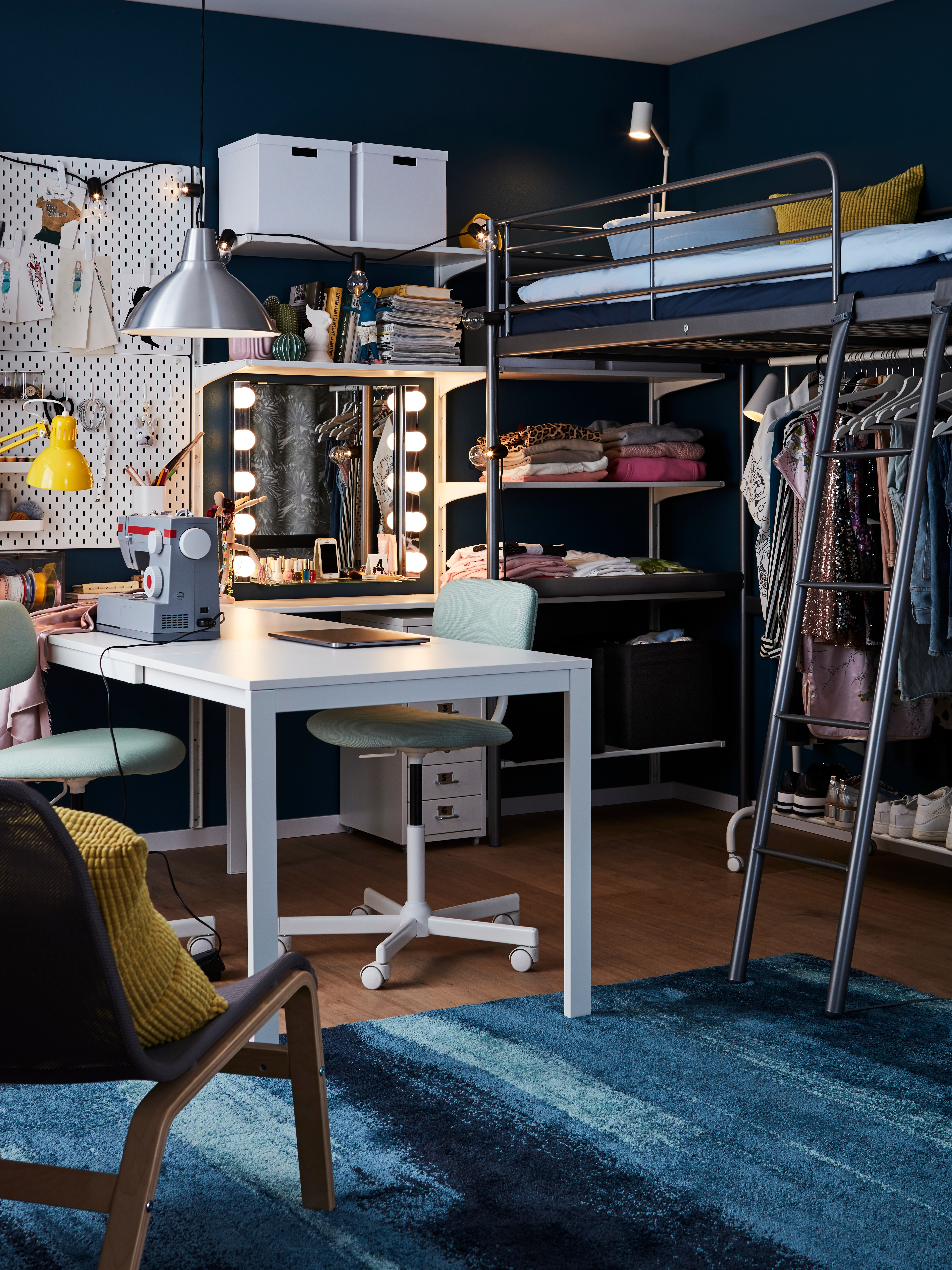 A silver-colour, steel SVÄRTA loft bed frame is in the corner of a room, with a clothes rack below and a sewing table nearby.