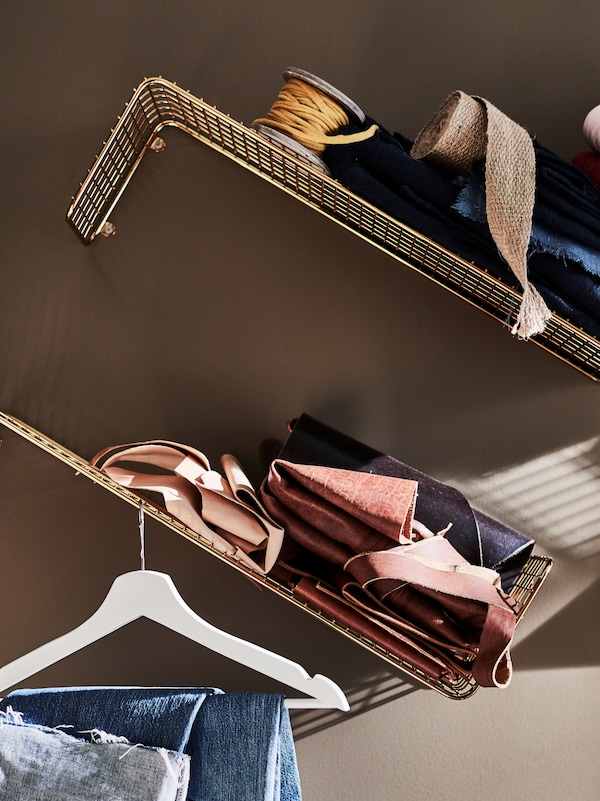 Two gold-colour SVENSHULT wall shelves attached to the wall on top of each other at an angle, holding folded fabric.