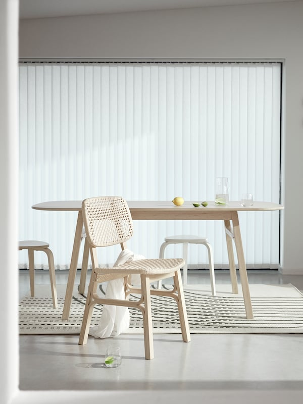 A brightly lit dining area is minimally furnished with the VOXLÖV bamboo chair, the VOXLÖV dining table and 2 stools.