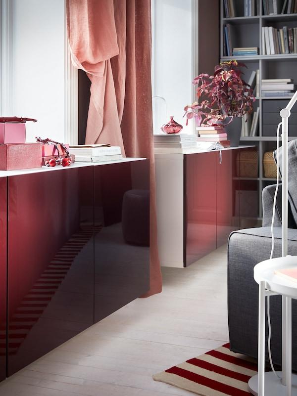 مجموعة خزانة BESTÅ بأبواب فائقة اللمعان بلون أحمر داكن ـ بني مثبتة بالحائط أسفل نافذة.