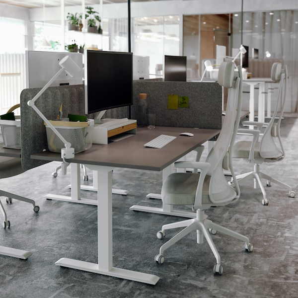 Workspaces divided by felt screens in an open-plan office, with brown and white desks, white office chairs and white lamps.