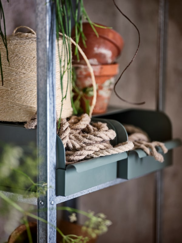 En HYLLIS reol til udendørs brug med to REJSA bokse med reb i.