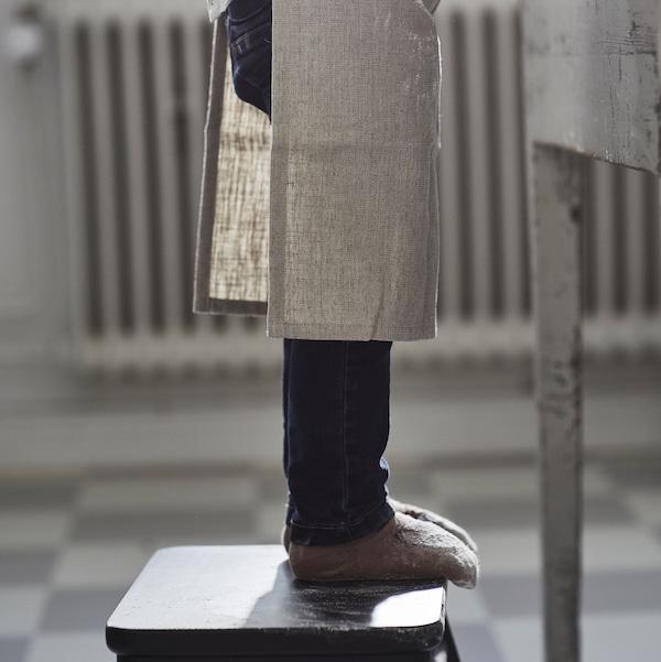 Na stoličce vedle stolu stojí dítě vdžínách, ponožkách abéžové zástěře kolekce MARIATHERES.