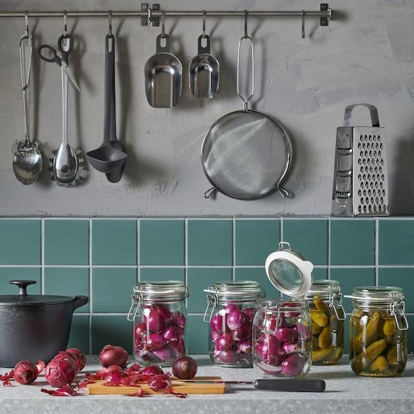 Plusieurs bocaux KORKEN reposent sur un comptoir de cuisine et des accessoires de cuisines sont suspendus à un mur en arrière-plan.