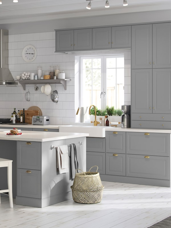 A kitchen with white tiled walls, BODBYN kitchen cabinets and fronts in grey with brass coloured knobs and handles.