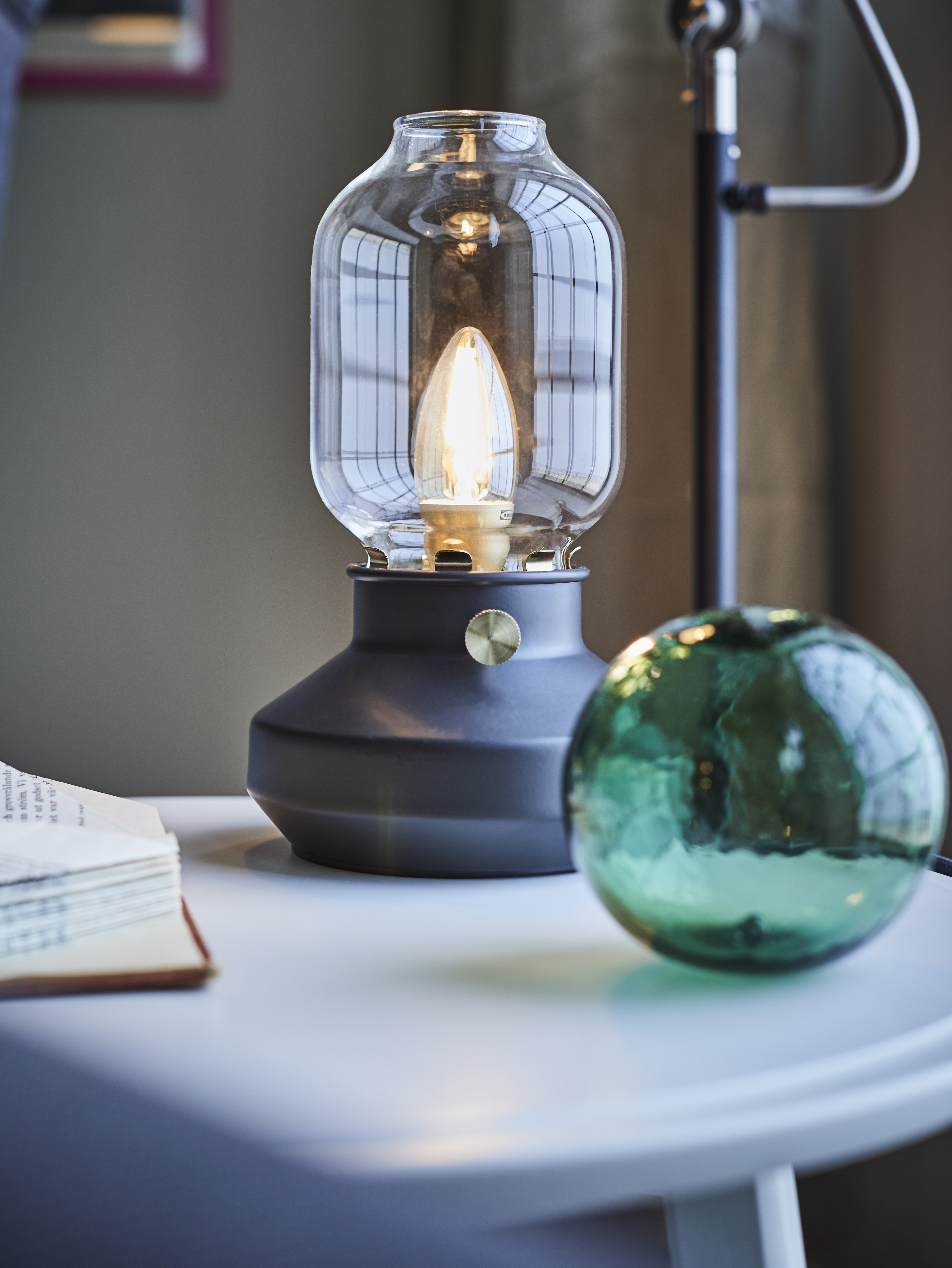 A table has an anthracite TÄRNABY table lamp with a glass shade, visible bulb and steel base resembling a kerosene lamp.