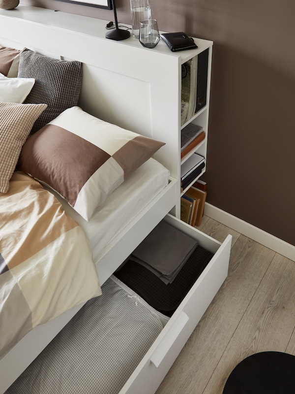 Weißes Bett mit Bettkasten und Kopfteil mit Stauraum