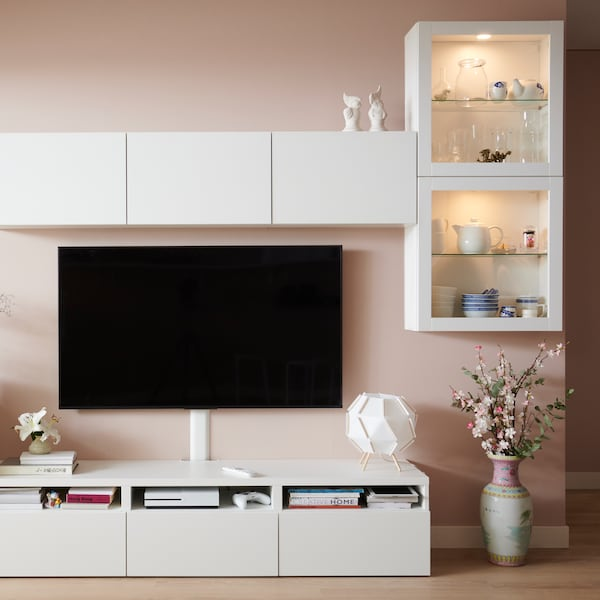 A TV sits on a wall above a white BESTÅ TV bench. BESTÅ cabinets with white and glass doors sit on the wall above the TV.