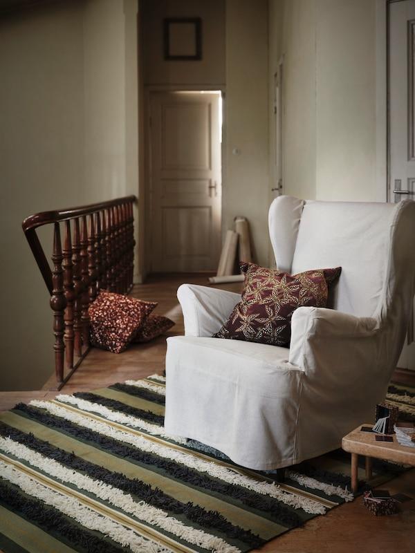 Un fauteuil STRANDMON recouvert d'une housse beige et orné d'un coussin rouge et or, installé sur un tapis en haut d'un escalier.
