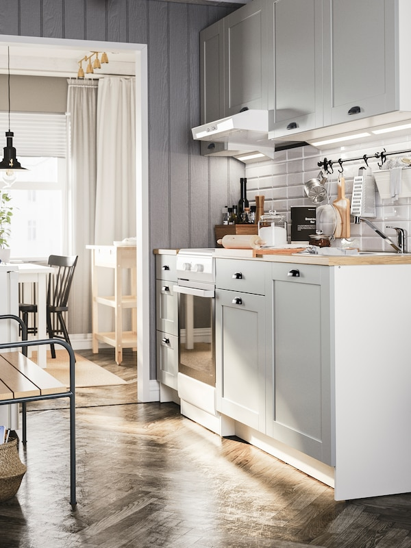 A grey KNOXHULT kitchen with wall cabinets and base cabinets, a white oven, kitchen utensils hang from hooks on a rail.