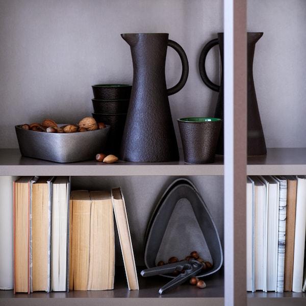 Musta VINTER 2021 -kivitavara on kirjahyllyllä, jossa on kulho, muki ja pähkinänsärkijä.