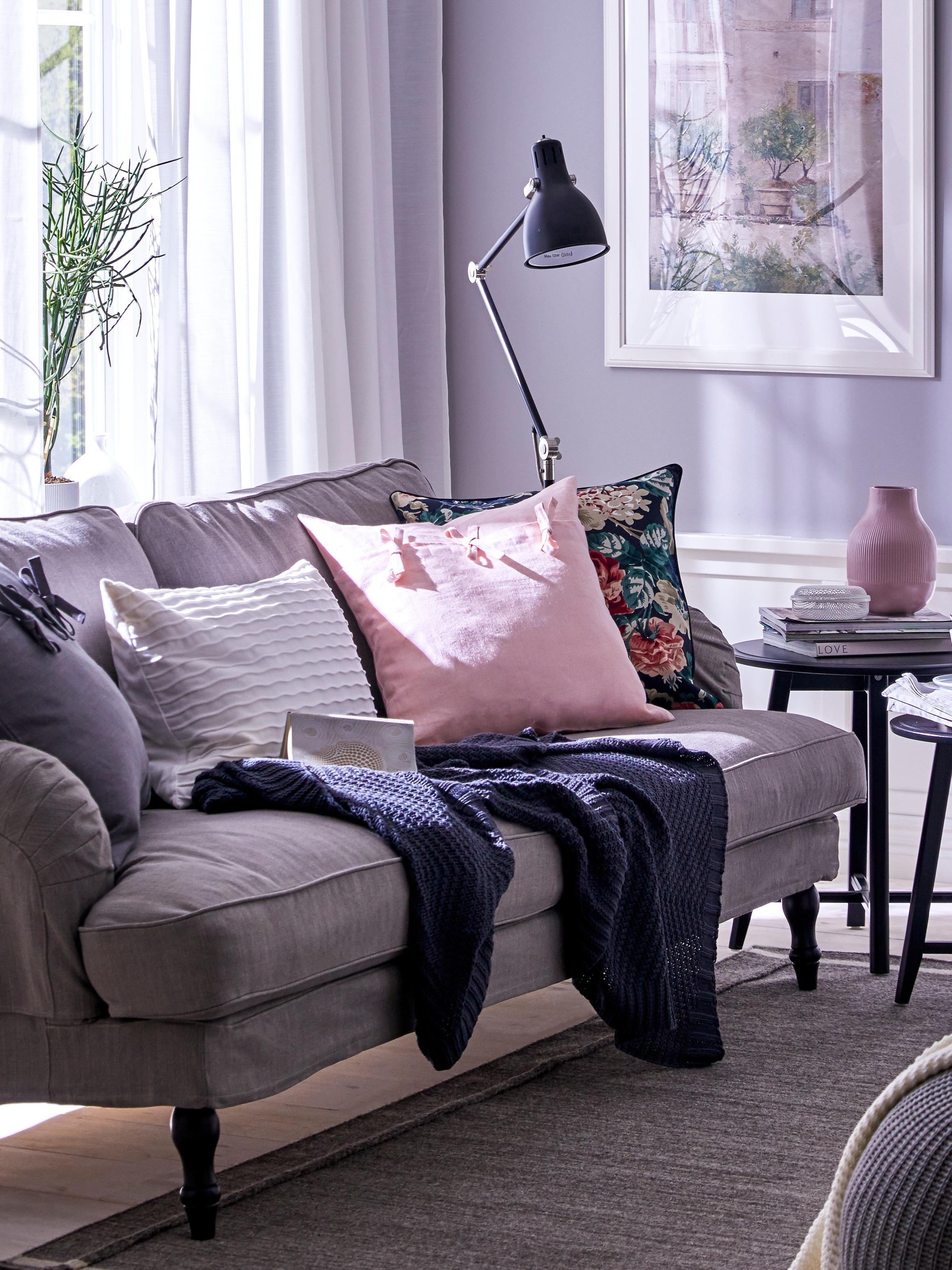 Siva STOCKSUND sofa u dnevnoj sobi s lila zidovima, na njoj su ukrasni jastuci s AINA i LEIKNY navlakama te tamnosiva JENNYANN lagana deka.