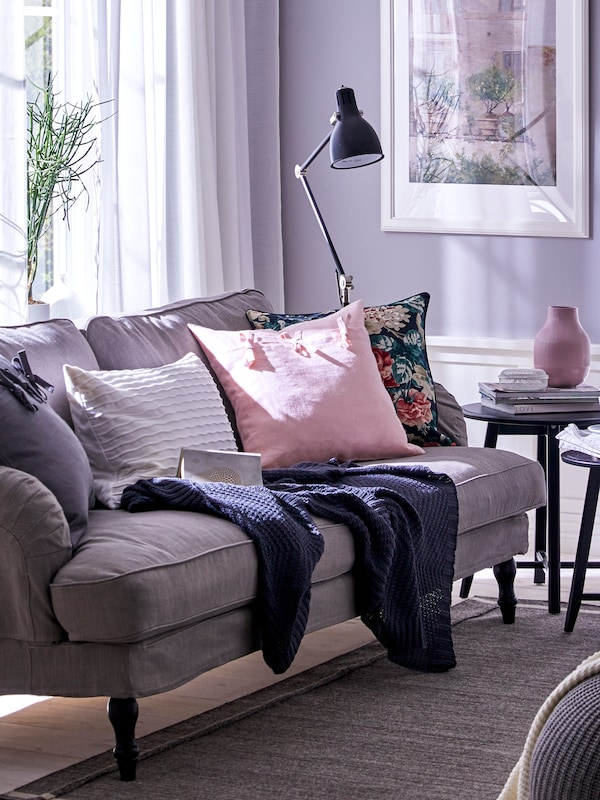 A throw and some cushions, including one in a light pink AINA cushion cover, lie on a sofa near a window in a living room.