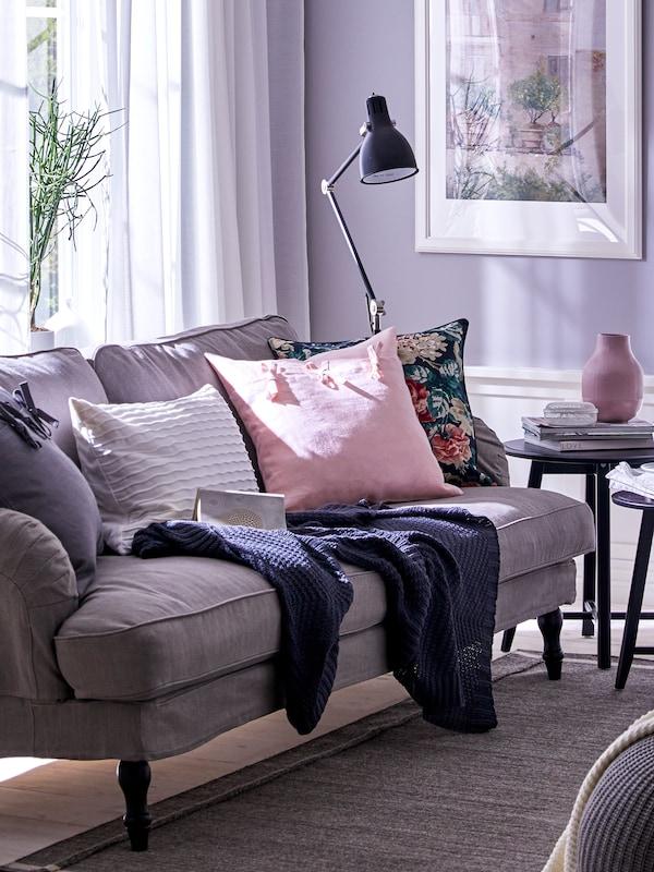 In un soggiorno, un plaid e dei cuscini, uno con fodera AINA rosa pallido, su un divano vicino a una finestra - IKEA