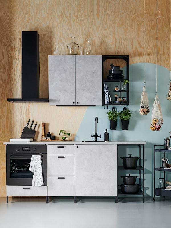 ENHET kuhinja s kombinacijom zatvorenih elemenata za odlaganje, u mermernoj sivoj, i crnih otvorenih polica, naspram drvenog zida.