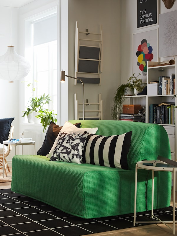 A LYCKSELE LÖVÅS 2-seat sofa-bed with a VANSBRO bright green cover and various cushions on top in a small studio.