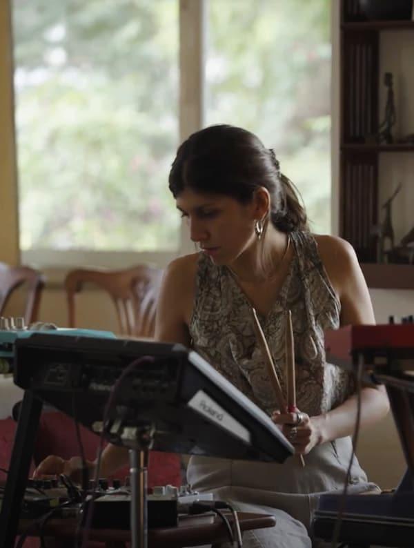 Egy nő egy monitorral szemben ül, és dobütőket tart a kezében.