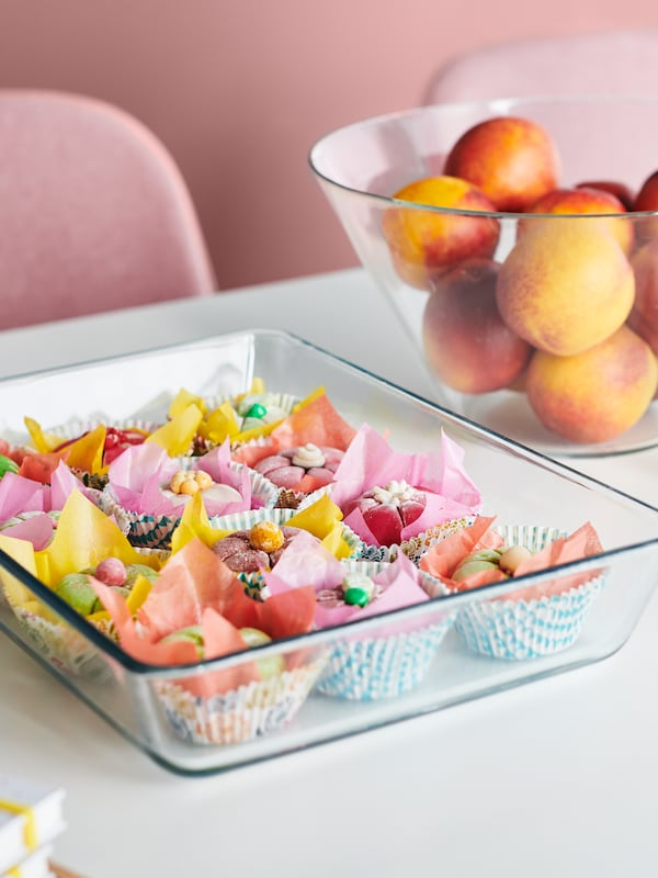 A flat glass serving dish filled with colourful cakes, beside a deeper glass dish full of fruit on a white table top.