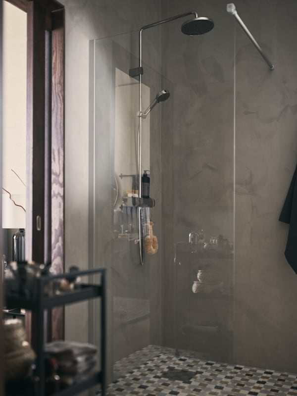 Cabine de duche com paredes cinzentas e porta de vidro.