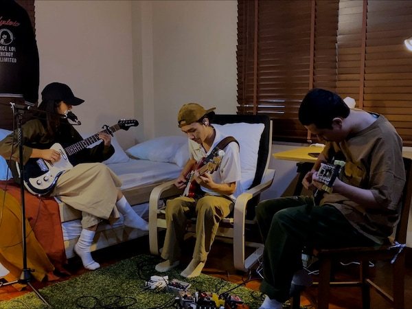 Band Yonlapa sitting in a bedroom playing guitars.