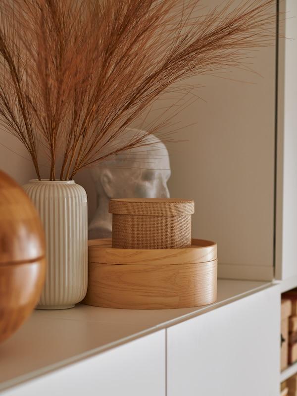 Une boîte KVARNVIK, une boîte avec couvercle MALLGRODA en placage de frêne, un vase et un buste en céramique décorant le dessus d'une armoire blanche.