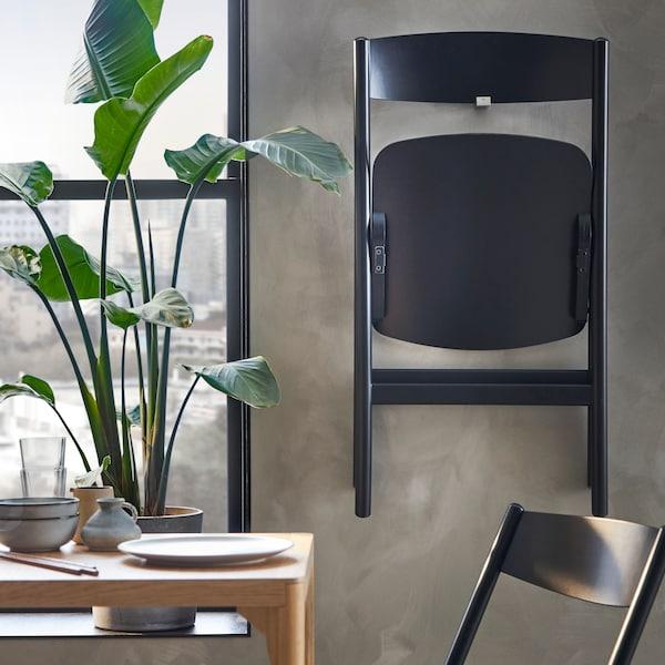 En RÅVAROR stol är upphäng på en vägg.