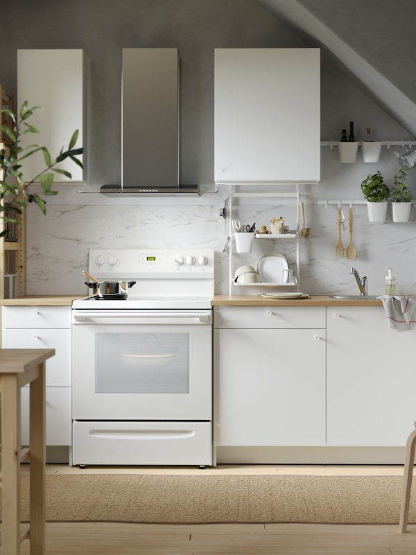 A white KNOXHULT kitchen with base and wall cabinets with white marble effect splashbacks and kitchen utensils hanging on rails with hooks.